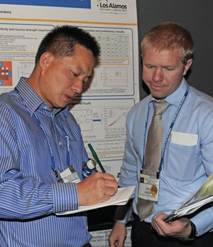 """Picture (Courtesy of ARQ): John Auxier (right) and Jianwei Hu, a research assistant at Los Alamos National Laboratory, discuss Hu's poster on """"Quantifying fissile content in spent fuel assemblies using the 252Cf interrogation prompt neutron (CIPN) technique."""""""